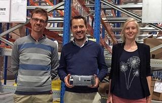 CIO van Essers Erik Lamoral poseert met het eerste prototype en wordt geflankeerd door Ruben Smits (links) en Marieke Copejans (rechts), medewerkers van partner Intermodalics.