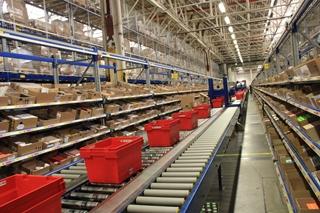 Vandaag levert de combinatie van de OSR met het pick-to-light systeem uitstekend werk. Een conveyorsysteem doorkruist het hele magazijn om de orderbakken naar de juiste zone te brengen.