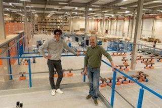 """Jeroen Dekker (links), hier naast medeoprichter Jean Lahaye in het e-fulfilmentcenter in Roosendaal: """"Door met robots te werken creëer je net een meer menselijke werksfeer en een aangenamer kader om binnen te functioneren."""""""