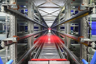 Het shuttlesysteem biedt ruimte voor 33.000 kunststof bakken. De 75 shuttles, verdeeld over drie gangen, zijn samen in staat 2400 bakken per uur te transporteren naar de acht orderpickstations.